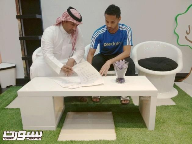 الشعلان واللاعب هادي اثناء التوقيع