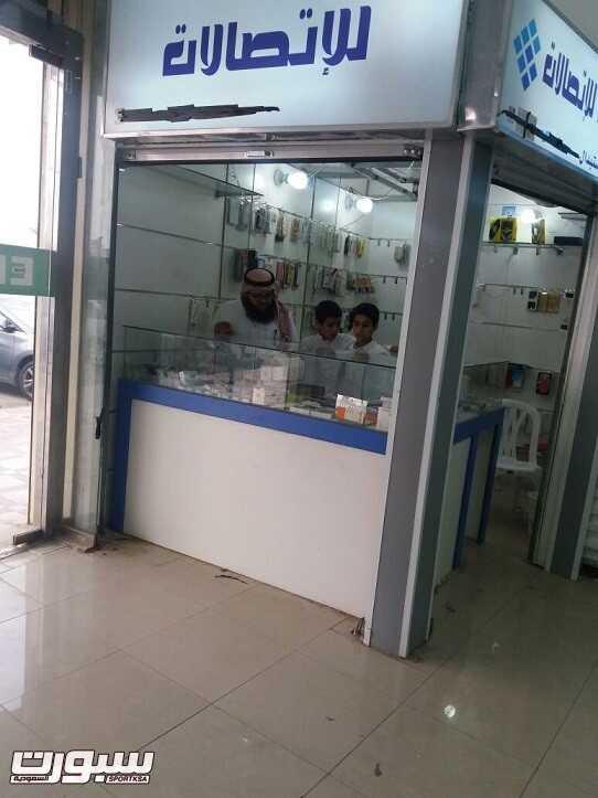 الأب برفقة ابنائه داخل محله التجاري الخاص بمجال الاتصالات