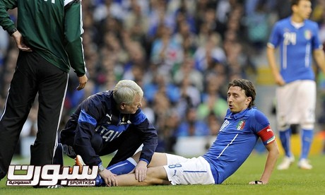 Riccardo Montolivo receives treatment to his left leg before being carried off on a stretcher